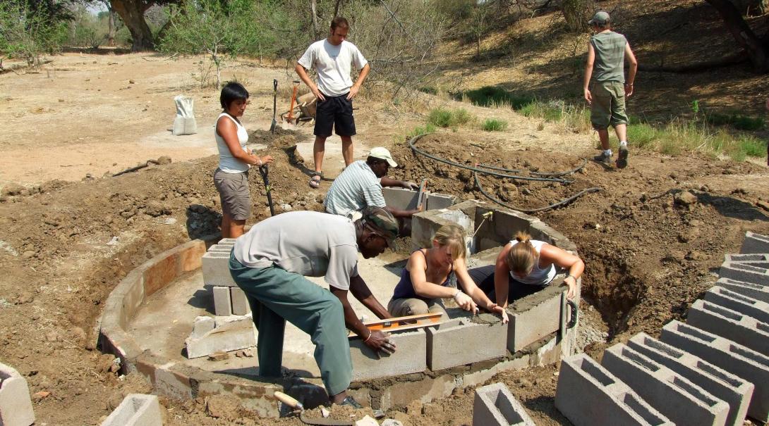 Teenage volunteers working on wildlife conservation by building water holes.